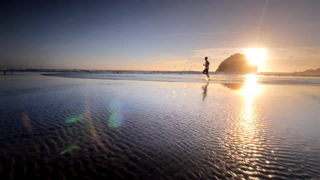 teen boy jogging on pacific beach at sunset - motivation stock videos & royalty-free footage