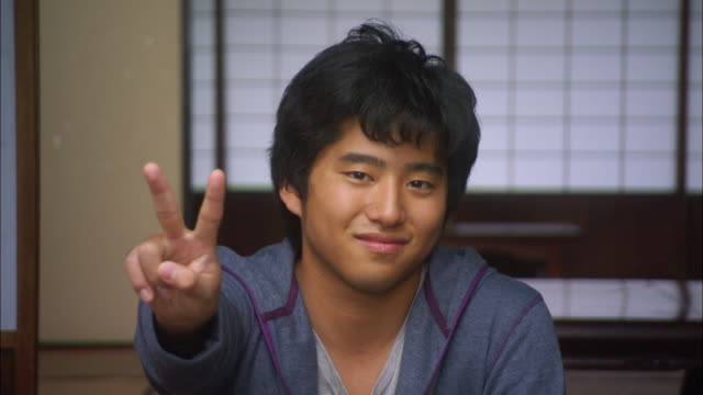 CU PORTRAIT Teen boy making peace sign/ Tokyo, Japan