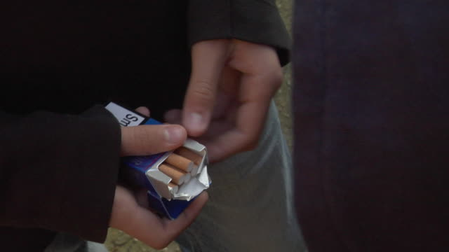 shaky cu teen boy offering another boy cigarette from package / london, england - zigarette stock-videos und b-roll-filmmaterial