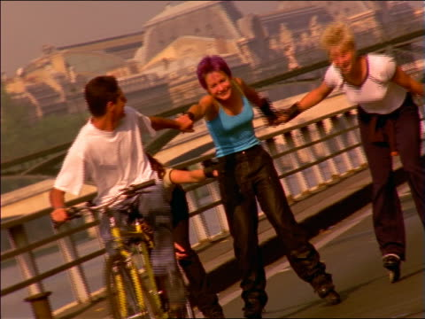 vidéos et rushes de teen boy on bike pulling 3 teen inline skating girls on path by seine / paris, france - 1990 1999