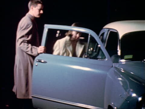 1953 teen boy opening car door for girl in formalwear at night / educational - high school prom stock videos and b-roll footage