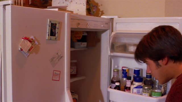 a teen boy opens the refrigerator and drinks milk from the jug. - refrigerator stock videos & royalty-free footage
