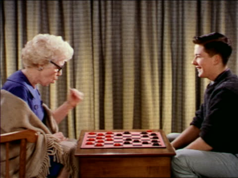 1962 PROFILE teen boy playing checkers with senior woman indoors / industrial