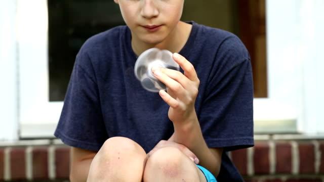 teen boy mit fidget spinner im freien spielen - männlicher teenager stock-videos und b-roll-filmmaterial