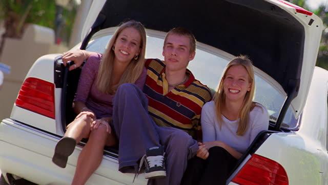 canted portrait teen boy + two teen girls sitting in open car trunk / boy hugging girls - 男性と複数の女性点の映像素材/bロール