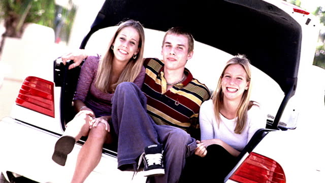 overexposed canted portrait teen boy + two teen girls sitting in open car trunk / boy hugging girls - 男性と複数の女性点の映像素材/bロール