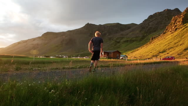 teen boy walking in grassy field in iceland at sunset - one teenage boy only stock videos & royalty-free footage