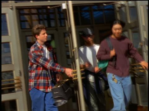 vídeos de stock, filmes e b-roll de 3 teen boys (1 asian) exiting school / 1 takes the other's hat from him - 1990 1999