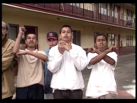 vídeos de stock e filmes b-roll de teen boys gesturing and making hand signs in aftermath of riots / los angeles, california, usa - 1992