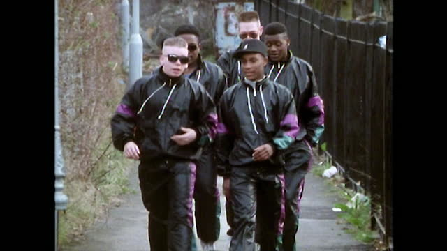 vídeos de stock e filmes b-roll de teen boys in tracksuits and high tops walk on street; 1989 - cultura hip hop