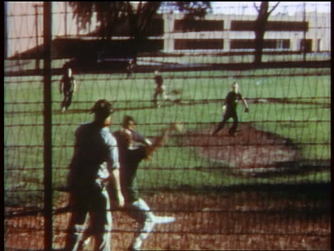 1957 teen boys playing softball / batter hits ball, catcher catches it / educational - 1957 stock-videos und b-roll-filmmaterial