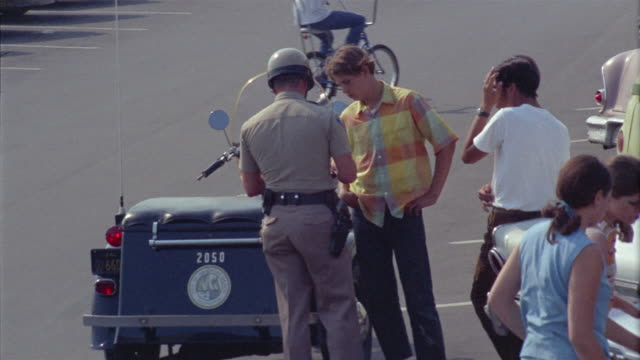 ms teen boys talking with traffic cop in street / newport beach, california, usa - 1966 stock videos and b-roll footage