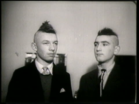 B/W 1951 2 teen boys with new mohawks in barbershop turning / France / newsreel