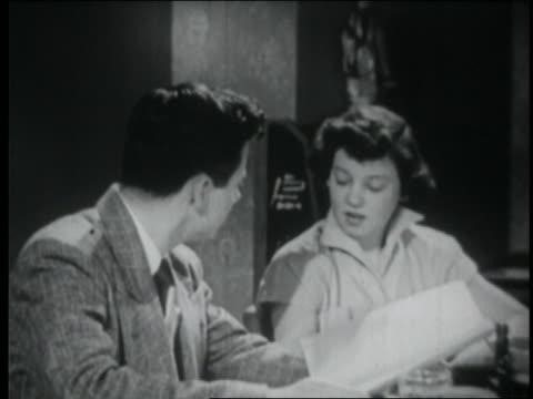 b/w 1950 teen couple having awkward conversation at table in restaurant - coppia di adolescenti video stock e b–roll