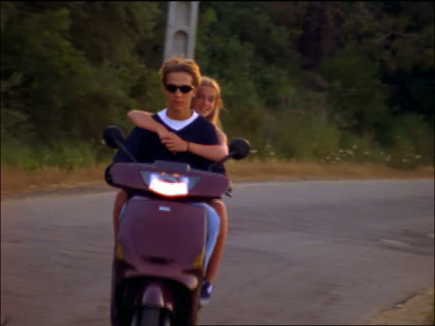 Teen couple riding moped towards camera / girl blows kiss at camera / Corsica