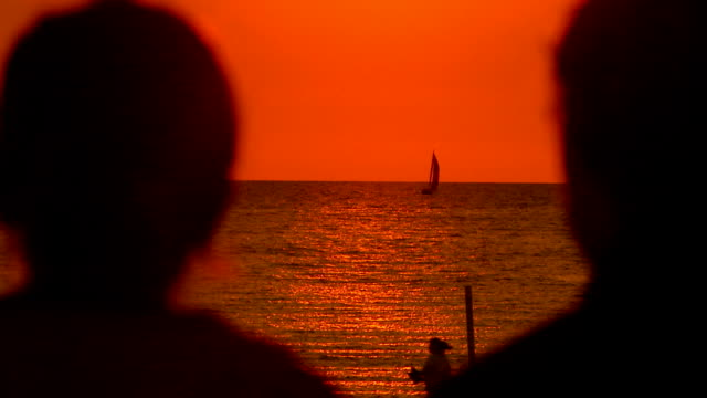 teen couple sitting at the beach watching the sunset - teenagerpaar stock-videos und b-roll-filmmaterial