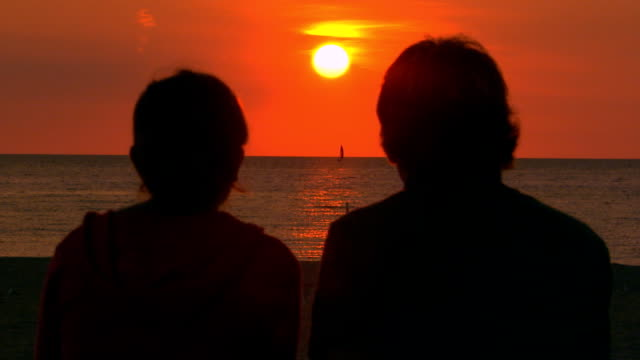 vidéos et rushes de teen couple sitting at the beach watching the sunset - couple d'adolescents