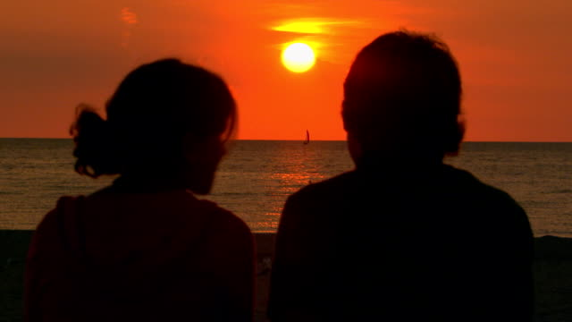 vidéos et rushes de teen couple sitting at the beach watching the sunset - petite amie