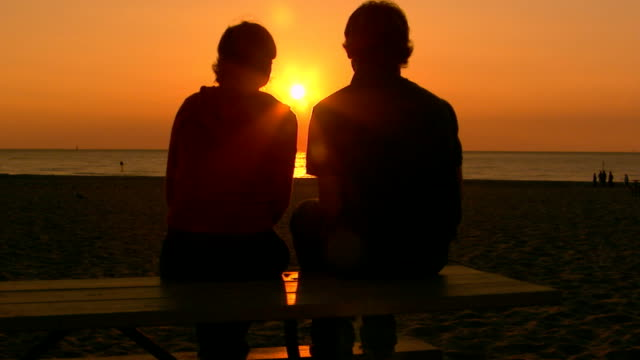vidéos et rushes de teen couple sitting on a picnic table at the beach watching the sunset - petite amie