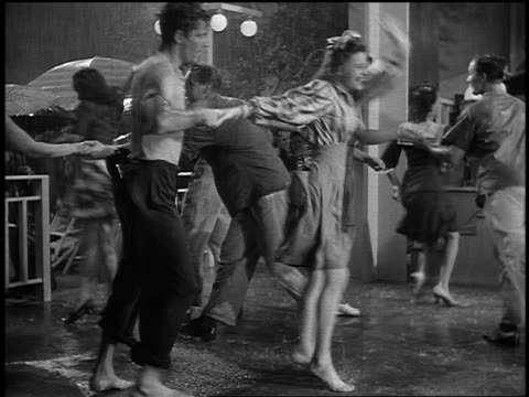 vidéos et rushes de b/w 1943 pan teen couples jitterbugging in rain with benny goodman band in background - rock