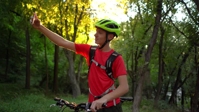 teen cyclist taking selfie in nature - one teenage boy only stock videos & royalty-free footage