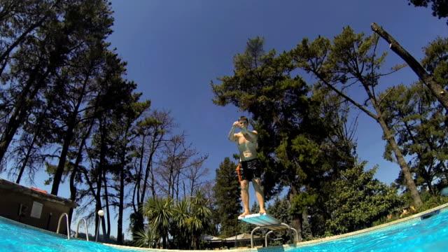 vídeos de stock e filmes b-roll de teen mergulhando em uma piscina - trampolim equipamento desportivo