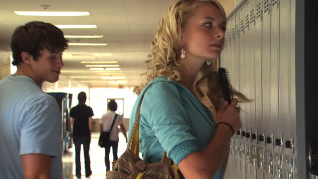 teen girl brushing hair in a school hallway - see other clips from this shoot 1148 stock videos and b-roll footage