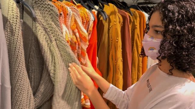 vídeos de stock, filmes e b-roll de adolescente escolhendo roupas na loja durante uma pandemia coronavírus - shopping center