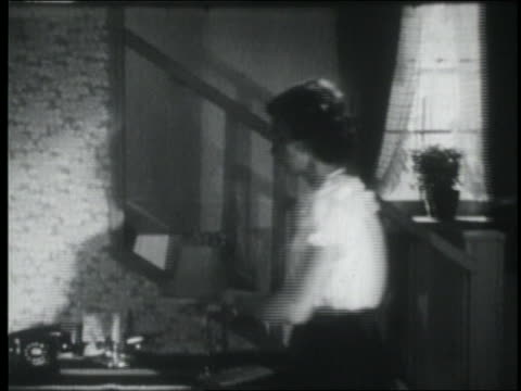 b/w 1953 teen girl coming downstairs + answering telephone / talks to mother in foreground - arguing stock videos & royalty-free footage