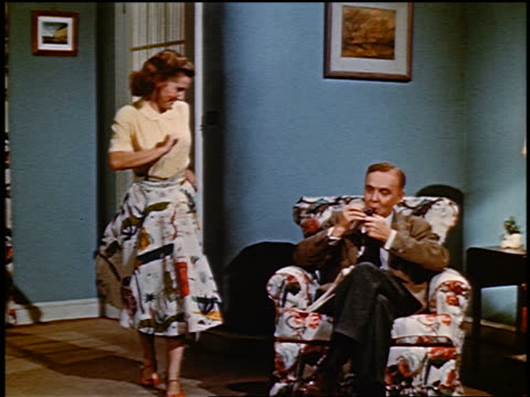 vidéos et rushes de 1952 teen girl dancing next to man sitting in chair lighting pipe in living room - 1952