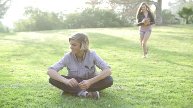 ms pan teen girl dumping leaves on boy in grass field / los angeles, california, united states  - korslagda ben bildbanksvideor och videomaterial från bakom kulisserna