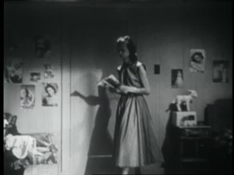 b/w 1953 teen girl entering room reading magazine + sitting at vanity / starts doing her hair - solo adolescenti femmine video stock e b–roll