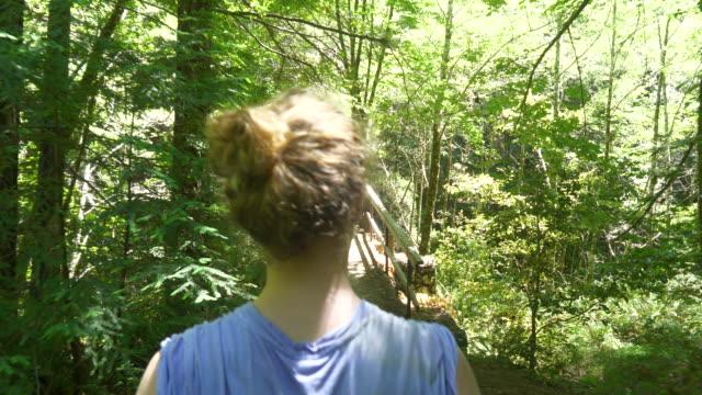 vídeos de stock, filmes e b-roll de teen girl hiking in forest and walking across wooden bridge - sequoia sempervirens