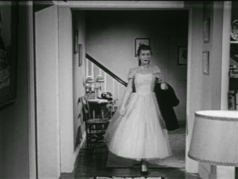 B/W 1953 teen girl in formal dress walking down stairs + entering room / boy helps with her coat