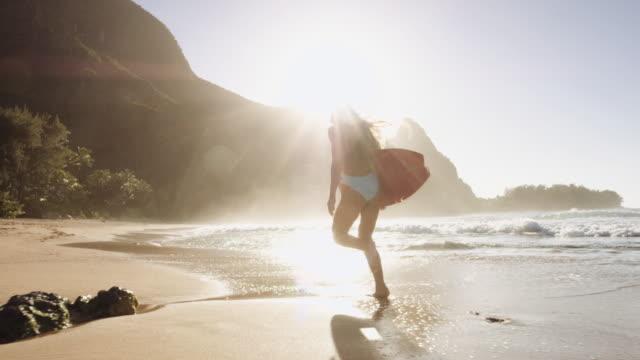 Teen girl jogging with surfboard