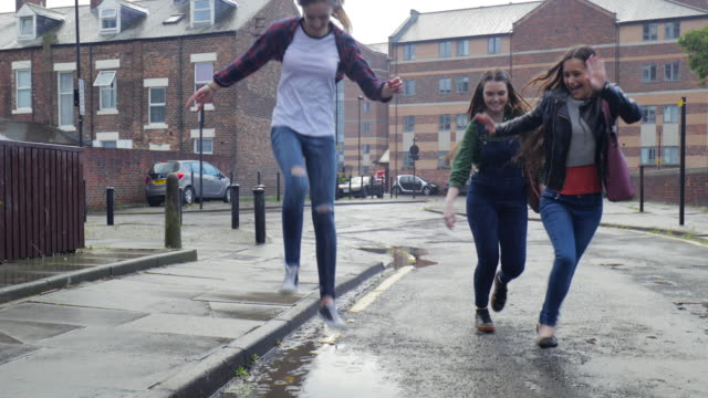 vídeos de stock e filmes b-roll de teen girl jumping into a puddle while its raining - teenage girls