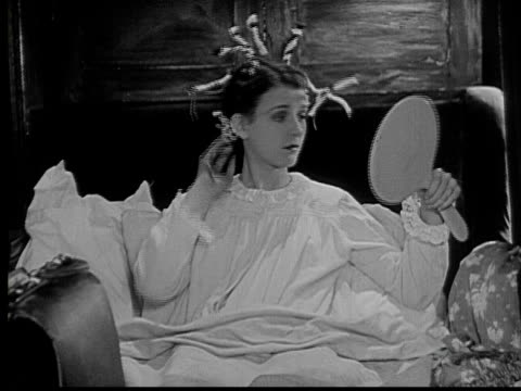 1924 b/w ms teen girl (marceline day) looking in mirror and adjusting rag curlers in her hair while sitting in her bed / usa - nightdress stock videos & royalty-free footage
