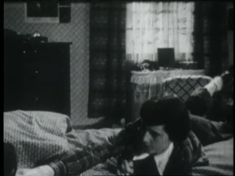 b/w 1953 teen girl lying on bed + writing in diary - weiblicher teenager allein stock-videos und b-roll-filmmaterial