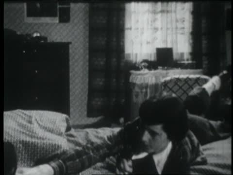b/w 1953 teen girl lying on bed + writing in diary - solo adolescenti femmine video stock e b–roll