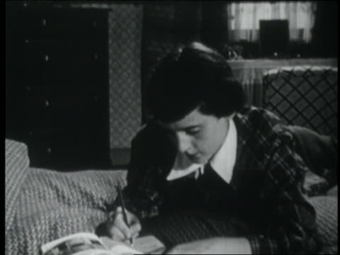 b/w 1953 teen girl lying on bed + writing in diary - diary stock videos & royalty-free footage