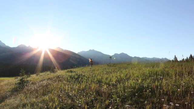 vídeos y material grabado en eventos de stock de teen girl runs across mtn meadow away from sunrise - sólo una adolescente