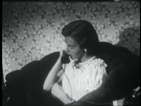 b/w 1953 teen girl sitting in armchair + talking on telephone - one teenage girl only stock-videos und b-roll-filmmaterial
