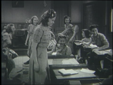 b/w 1940 teen girl slaps boy sitting at desk in classroom; students laugh, teacher enters - negative emotion stock videos & royalty-free footage