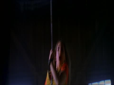 teen girl swinging on rope toward camera in abandoned warehouse - solo adolescenti femmine video stock e b–roll
