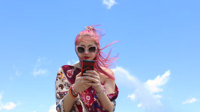 Teen Girl Using Phone Outdoors on Windy Day