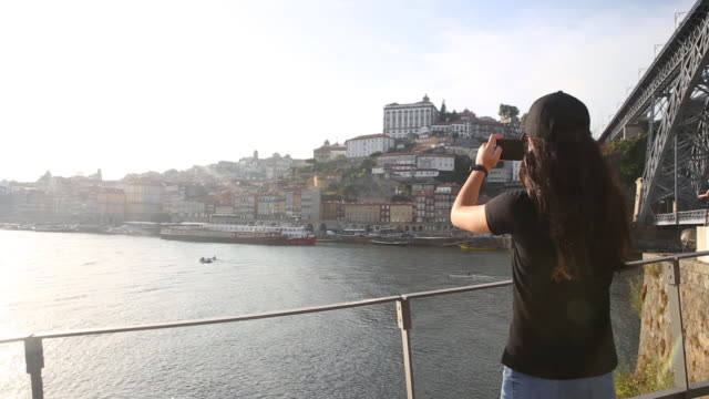teen girl with black cap photographing the beautiful city of porto from across the douro river - one teenage girl only stock videos & royalty-free footage