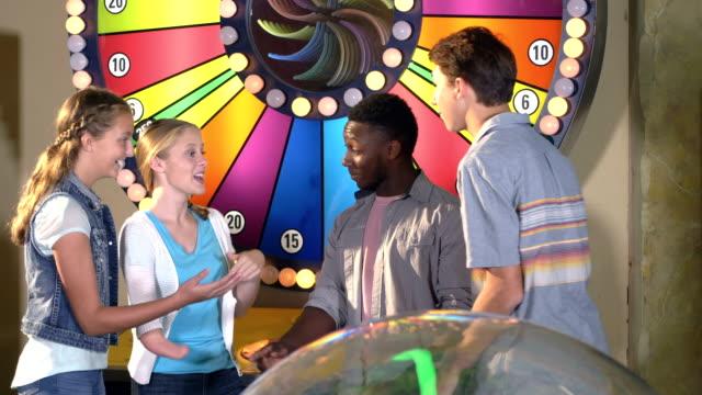 vídeos de stock e filmes b-roll de teen girl with malformed arm, friends, amusement arcade - 12 13 years