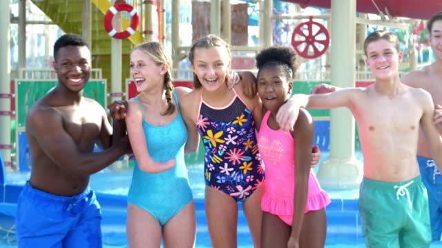 vídeos de stock, filmes e b-roll de menina adolescente com braço malformado, amigos no parque da água - 12 13 years