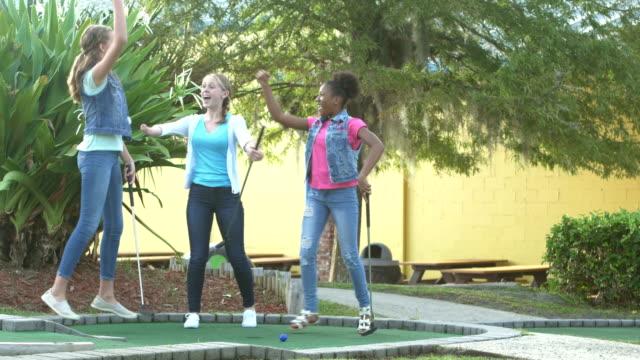 vídeos de stock e filmes b-roll de teen girl with malformed arm, friends, miniature golf - 12 13 years
