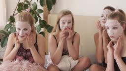 Teen girls applying cosmetic facial tissue mask